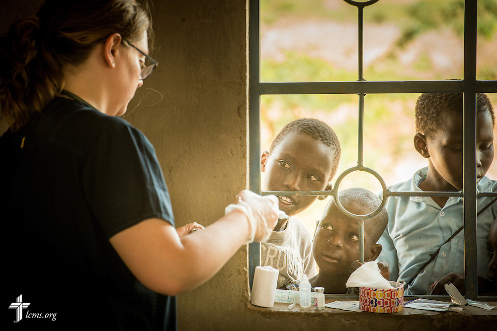 Boys watch as Sarah Kanoy, a career missionary in East Africa, treats a patient at the LCMS Mercy Medical Team on Monday, June 20, 2016, in Nataparkakono, a village in Turkana, Kenya.  LCMS Communications/Erik M. Lunsford