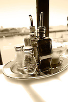 olive oil and vinegar,salt and pepper shaker on table with view of outside