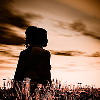 Silhouette of a young woman in a corn field