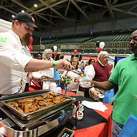 Ryan McCoy, Executive Chef at The Grill, serves a Sprin Roll to Anthony Macklin, of Tupelo, as Macklin passes by The Grill's booth during The Taste of Tupelo Thursday night at the BancorpSouth Arena in Tupelo.