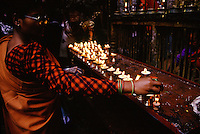 A woman lights butter lamps which are reflected in her glasses at the Golden Temple, Patan, Kathmandu