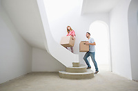 Couple carrying cardboard boxes up stairs in new house