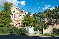 A couple walks past an old synagogue in Simferopol, Crimea, Ukraine. The communist Red Star sits over the outline of a Star of David, which was removed from this synagogue during the Soviet period. A new satellite dish is on the roof.