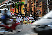 Ancient Hindu ritual at crossroads, while cars and motorbikes rush by.<br /> Sanur, Bali, Indonesia