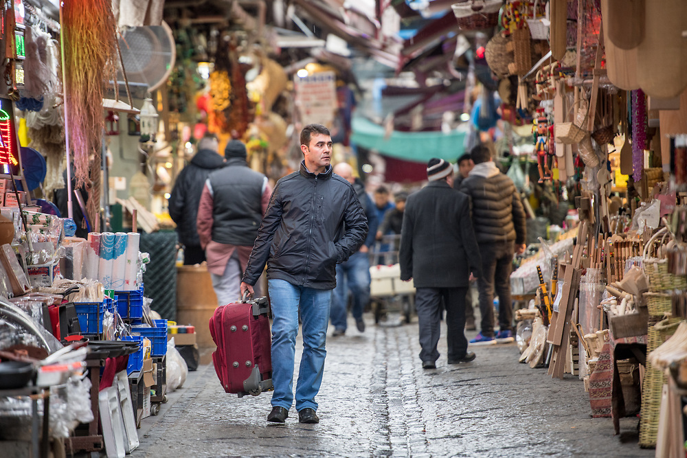 An adult male carries a piece of luggage while walking down a street of an outdoor marketplace, in Istanbul, Turkey