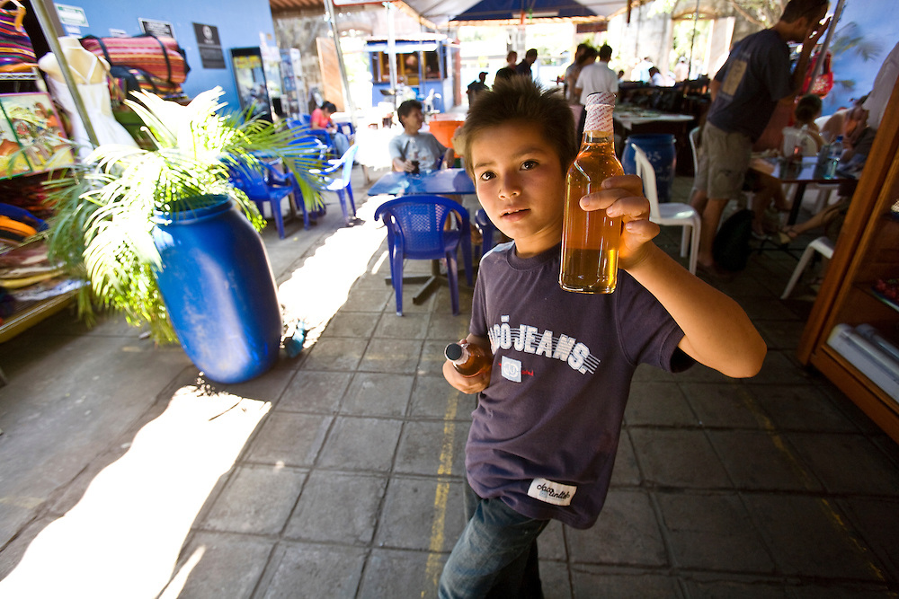 A street boy sells honey to tourists in Masaya. Masaya is close to Granada in Nicaragua. Masaya is famous for its art markets where it sells crafts from the surrounding region. It is also a major regional transport hub.