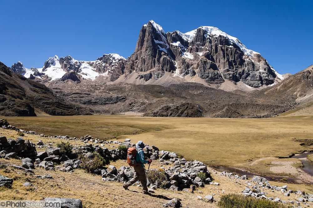 A trekker descends from San Antonio Pass into Huanacpatay Valley, with views of Nevado Cuyoc and Nevados Puscanturpa. Day 6 of 9 days trekking around the Cordillera Huayhuash in the Andes Mountains, Peru, South America.