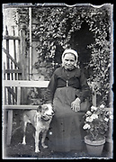 elderly woman sitting on a bench with dog in flower garden France circa 1930s