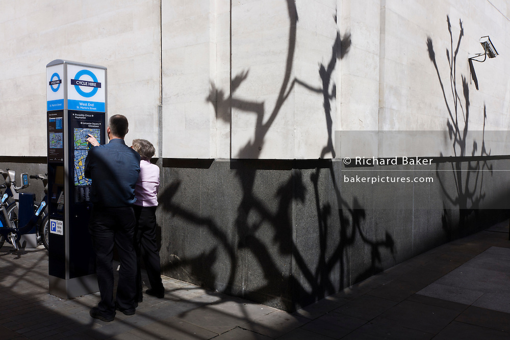 Visitors point to locations on a map of central London, with shadows of bare branches on wall.