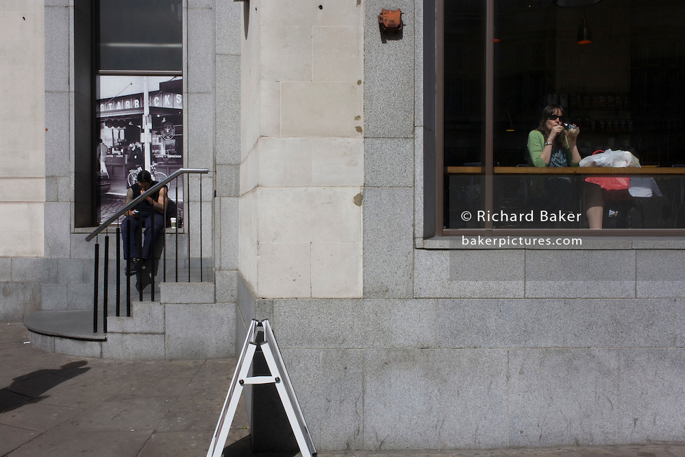 A Starbucks customer and a man outside sitting on a ledge in the City of London.