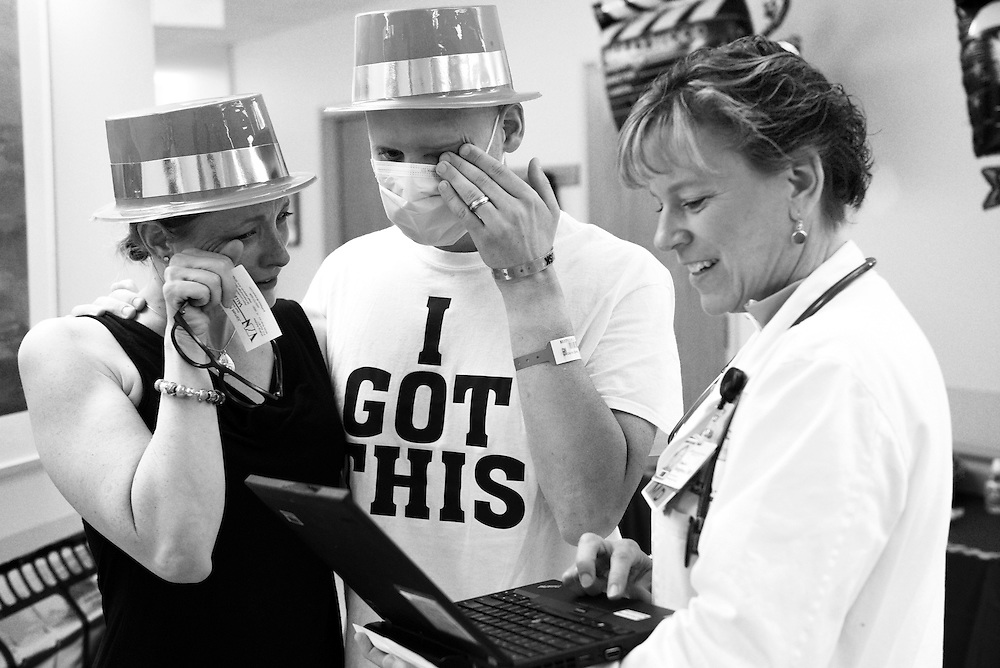 Chris Brown and his wife Alicia receive news that his recent bone marrow biopsy is free of leukemia from Dr. Elizabeth Bengston after a month in treatment and recovery in the inpatient oncology unit at DHMC in Lebanon, N.H. Saturday, July 11, 2015. The Browns wore plastic top hats while aiming to walk one mile in the unit's Hollywood themed indoor Prouty. Chris Brown, who is being treated for acute myeloid leukemia, plans to ride in next year's Prouty fundraiser following a stem cell transplant.  (Valley News - James M. Patterson)<br />