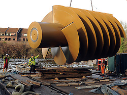 © Licensed to London News Pictures. 20/12/2011, Windsor, UK. One of the two giant 40 tonne Archimedes screws is lifted into place at Romney Weir on the River Thames. The screws, the largest in the UK and fish friendly, will generate 300 kilowatts of energy every hour to power Windsor Castle. It is the largest hydropower scheme in the South East of England. Photo credit: Stephen Simpson/LNP