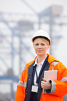 Female engineer holding tablet PC in shipping yard