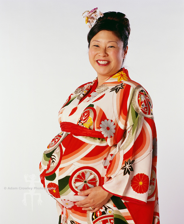 Pregnant woman in traditional Japanese kimono, smiling, portrait