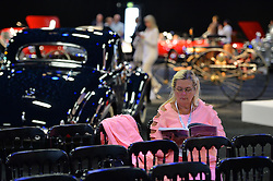 © Licensed to London News Pictures. 08/09/2013. London, England. RM Auctions Classic Car auction at Battersea Evolution, London. Photo credit : Mike King/LNP. RM Auctions 8-9 September 2013 at Battersea Evolution. A lady reads the sales catalogue.