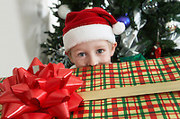 Boy (5-6) in Santa costume peeking over present by Christmas tree