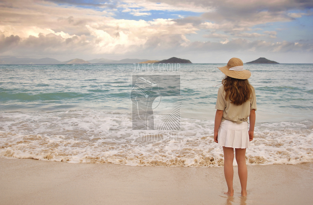 Girl looking out over a calm, tropical ocean in the early evening