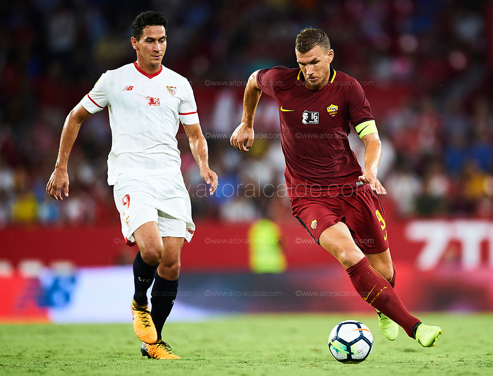 SEVILLE, SPAIN - AUGUST 10:  Edin Dzeko of AS Roma (R) competes for the ball with Paulo Henrique Ganso of Sevilla FC (L) during a Pre Season Friendly match between Sevilla FC and AS Roma at Estadio Ramon Sanchez Pizjuan on August 10, 2017 in Seville, Spain. (Photo by Aitor Alcalde/Getty Images)