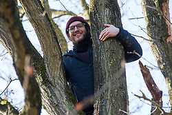 Harefield, UK. 18 January, 2020. Earth protector Quercus celebrates in the oak tree in Colne Valley wildlife protection camp in which he spent a day and a night avoiding the clutches of enforcement agents acting for HS2 earlier in the week. Activists from Extinction Rebellion, Stop HS2 and Save the Colne Valley today reoccupied the camp from which all but two activists had been evicted by bailiffs the previous week on the second day of a three-day 'Stand for the Trees' protest in the Colne Valley timed to coincide with tree felling work by HS2. 108 ancient woodlands are set to be destroyed by the high-speed rail link.