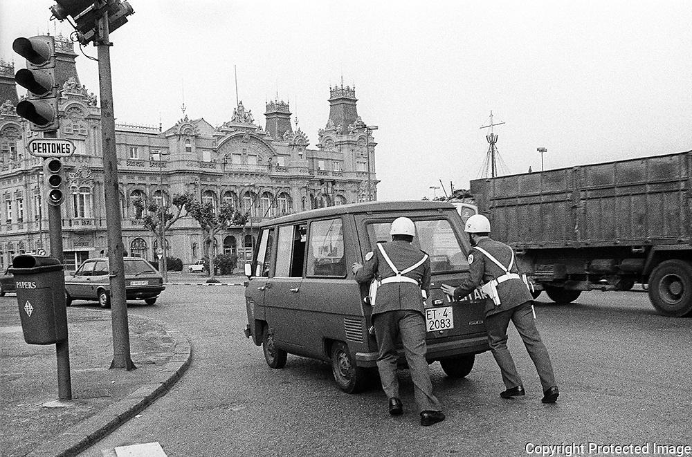 Dos policias militares empujan la furgoneta averiada modelo Vannette en la que viajaban, en la rotonda del monumento a Colón , al fondo el edificio de la Comandancia del Puerto de Barcelona, Noviembre de 1983. © Jordi Camí.