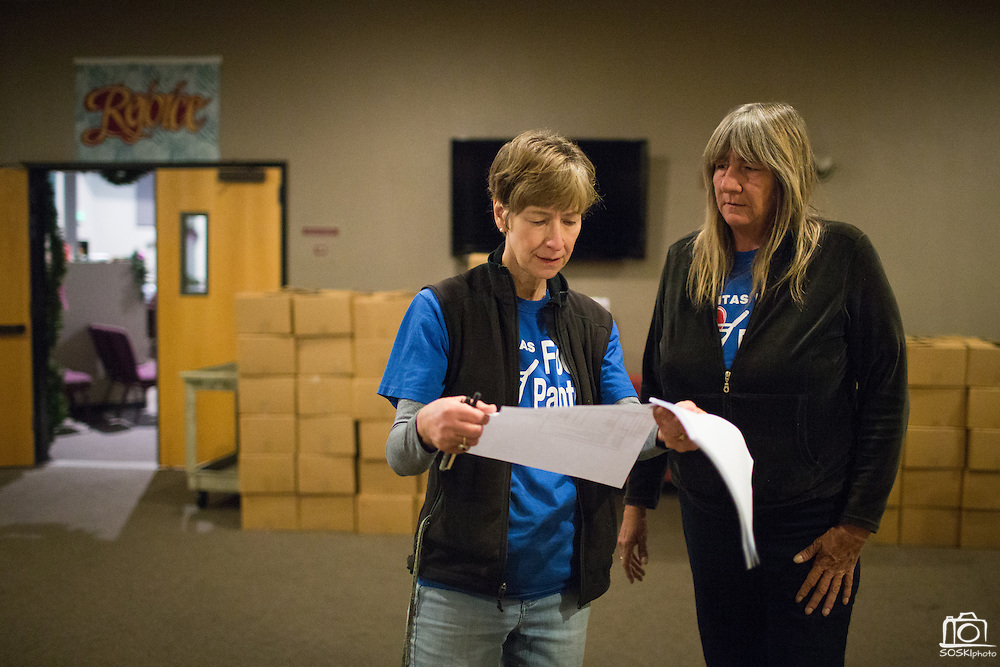 Milpitas Food Pantry Executive Director Karen Kolander, right, and her Executive Assistant Ellen Brutsch review a list of Beneficiaries during a Milpitas Food Pantry event at Lifegate Church in Milpitas, California, on November 25, 2013. (Stan Olszewski/SOSKIphoto)