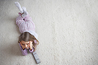 Girl (5-6) lying on rug view from above