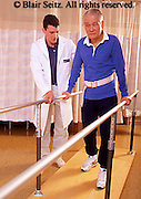 Medical Physical Therapy, Patient and Therapist, Caring Therapist, Male Physical Therapist Works with Elderly Male Patient, Male Physical Therapist with Patient on Parallel Bars