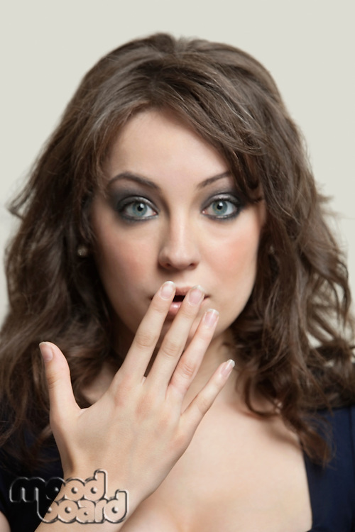 Close-up portrait of shocked young woman with hand over mouth against gray background