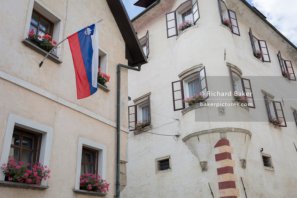 The Slovenian national flag hangs from a building in a rural central Slovenian town on the country's Independence Day, on 25th June 2018, in Skofja Loka, Slovenia.