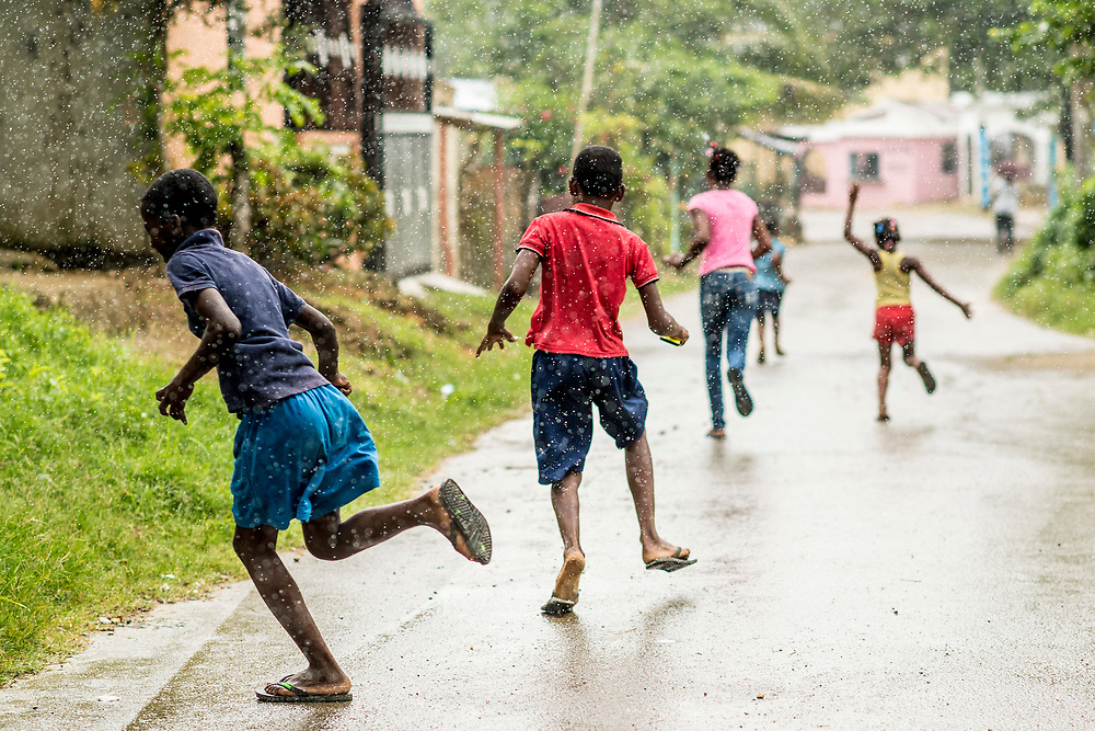 July 21, 2017, Boston, MA:<br /> Local kids run down the street in the rain in El Mam&oacute;n during the 2017 Lindos Sue&ntilde;os trip in the Dominican Republic Friday, July 21, 2017. <br /> (Photo by Billie Weiss/Boston Red Sox)