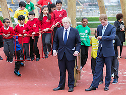 Prince Harry today joined Mayor of London Boris Johnson at the Olympic Park, London, United Kingdom. They officially opened a new playground for children and enjoyed some of the play obstacles on offer. Friday, 4th April 2014. Picture by i-Images<br /> <br /> Picture shows: Prince Harry checks his watch as Boris Johnson gigs a speech.