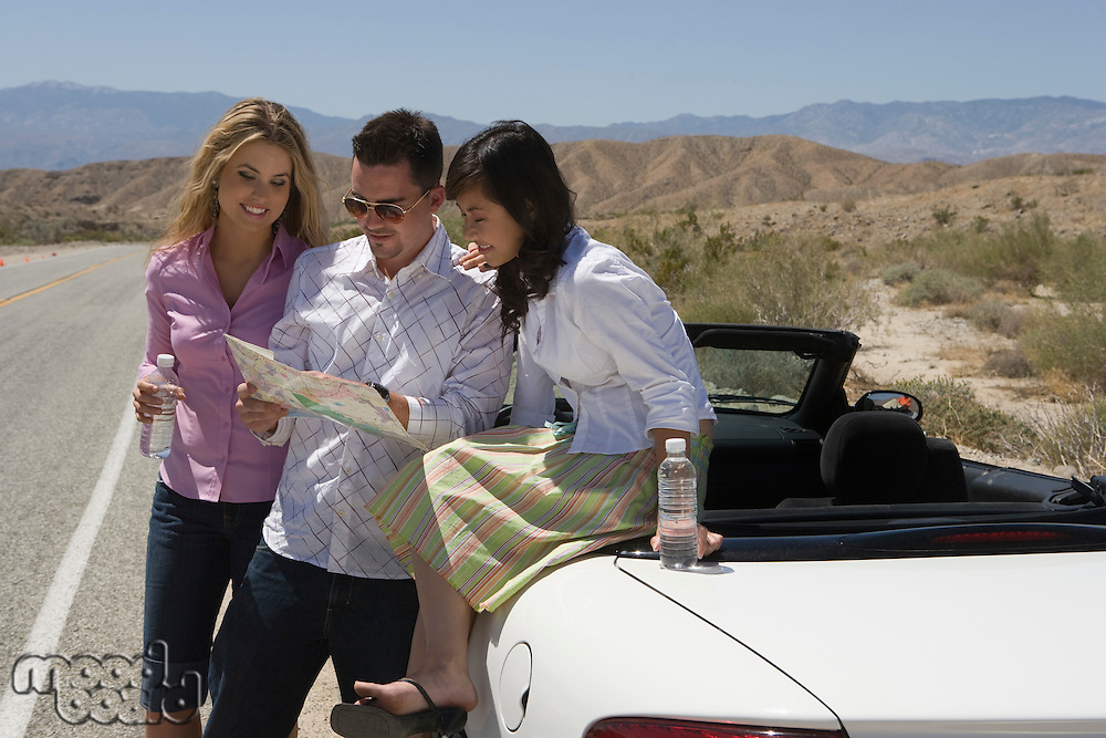 Three friends checking map at car in desert