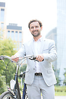 Portrait of happy businessman holding bicycle outdoors