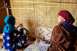 Women weaving a carpet in a  ruined, but still occupied,  kasbah near  Tazenakht, southern Morocco, Africa<br /> <br /> (c) Andrew Wilson | Edinburgh Elite media
