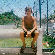 Young boy sitting on a concrete fence, Brazil