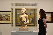 "© Licensed to London News Pictures. 15/11/2012. London, UK A woman looks at a sculpture by Henry Moore entitled ""Girl"" 1931. The Royal College of Art is celebrating its 175th anniversary with a major exhibition featuring more than 350 works of art and design by over 180 RCA graduates and staff, including Henry Moore, Barbara Hepworth, Tracey Emin, David Hockney, Peter Blake, Bridget Riley and Lucian Freud.  The RCA is the world's oldest art and design university in continuous operation. Its first students comprised a small group of teenage boys; today it educates some 1,200 postgraduate students from 55 different countries.. Photo credit : Stephen Simpson/LNP"