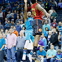 01 November 2015: Charlotte Hornets guard Kemba Walker (15) takes a jump shot over Atlanta Hawks guard Kent Bazemore (24) during the Atlanta Hawks 94-92 victory over the Charlotte Hornets, at the Time Warner Cable Arena, in Charlotte, North Carolina, USA.