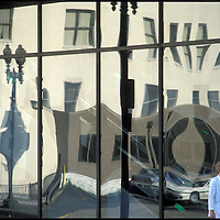 A pedestrian walks past the distorted reflection in a downtown Washington, DC building.
