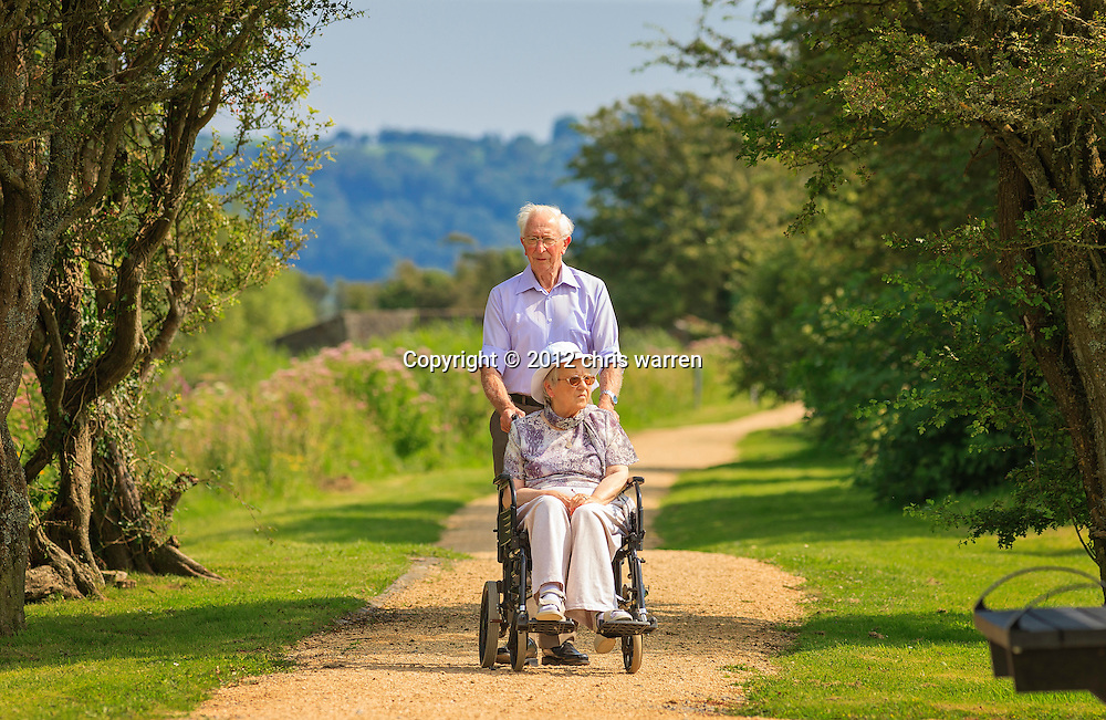 Senior couple - female wheelchair user and male - enjoying walk at Kidwelly Quay<br /> Gwendraeth Valley<br /> Carmarthenshire<br /> Valleys<br /> South<br /> Walking<br /> Activities and Sports