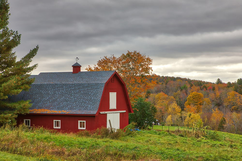 Rustic red barn along Massachusetts Route 8A in the Berkshires of Western Mass. The fall foliage colors and this farm setting immediately inspired me to stop on my way up to Vermont. An overcast with some dramatic cloud cover beautifully balanced the light and hues and provided superb photography condition. <br />