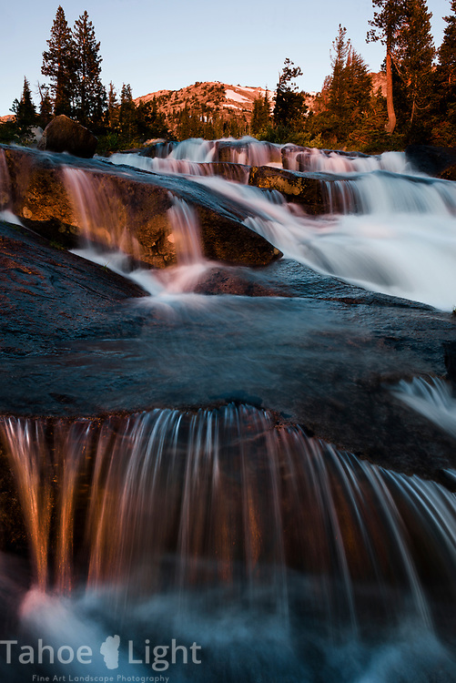 Flowing water out of  Fontanelles lake in Desolation Wilderness at sunrise.