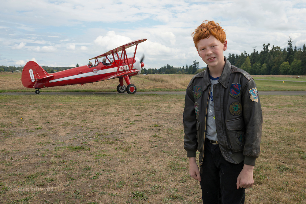 A young lad in his flight jacket, as a biplane taxis for takeoff at a small airshow.