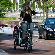 NLD/Amsterdam/20130606 - Alicia Keys met zoontje op de fiets in Amsterdam onderweg naar haar hotel - Alicia Keys on her bike with her son Egypt, driving to the city of Amsterdam before her concert tour
