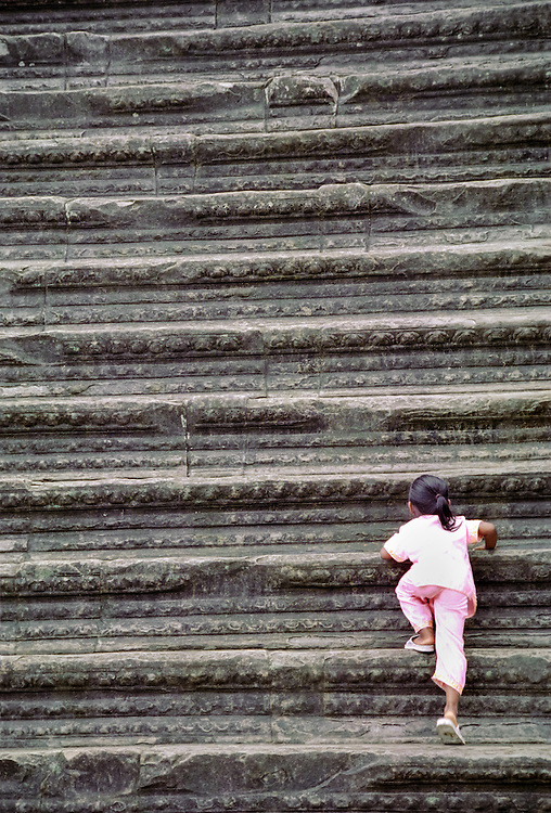 A young girl climbs up the stairs leading to the main sanctuary in Angkor Wat temple in the ancient city of Angkor. The steep, difficult to climb stairs symbolize the arduous path to reach Nirvana. Cambodia, 2003.