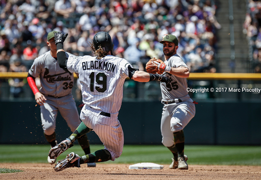 SHOT 5/28/17 12:57:43 PM - Colorado Rockies outfielder Charlie Blackmon #19 attempts to break up a double play in front of the St. Louis Cardinals' Greg Garcia #35 and Aledyms Diaz #36 at Coors Field in Denver, Co. The Rockies won the game 8-4. (Photo by Marc Piscotty / © 2017)