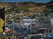 London Street, Lyttelton, New Zealand, street scene with shoppers and cyclists, the Port Hills in the backgound