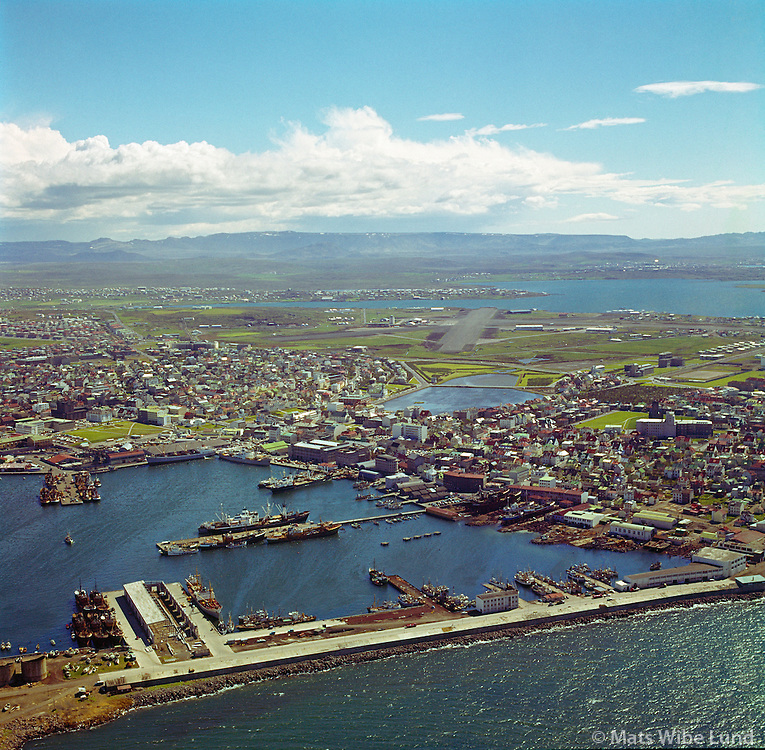 Reykjavíkurhöfn 1963, miðbær og Reykjavíkurflugvöllur í baksýni. Séð til suðurs.  /   Reykjavik harbour 1963. Capital centre, lake Tjornin and Reykjavik domestic airport. Viewing south.