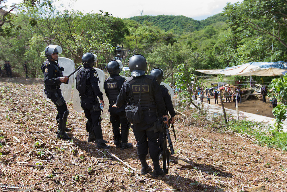 Police officers watch and prepare to launch tear gas on to the locals that continue to resist in front of the El Tambor mine. After two years and two months of peacefully blocking the entrance to U.S.-based Kappes, Cassiday & Associates (KCA) El Tambor gold mine, local residents of San Jose del Golfo and San Pedro Ayampuc were violently evicted by Guatemalan Police forces in order to introduce heavy machinery inside the industrial site. La Puya, San Pedro Ayampuc, Guatemala. May 23, 2014.