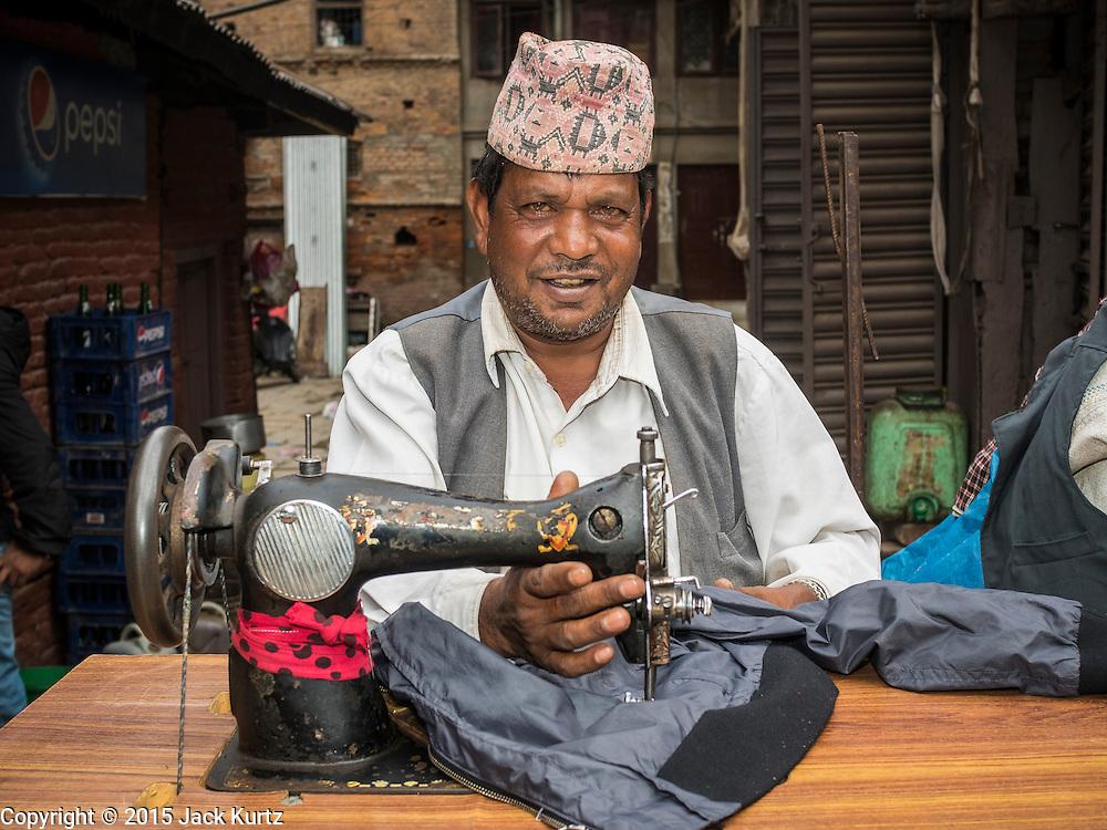 01 AUGUST 2015 - KATHMANDU, NEPAL: A Nepalese tailor works with his treadle sewing machine on a street corner in the Thamel neighborhood of Kathmandu.      PHOTO BY JACK KURTZ