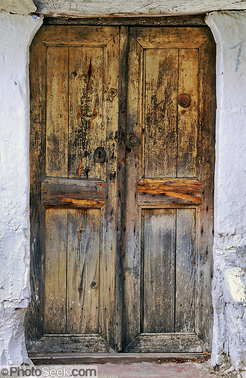 Old wood door with faded yellow paint, in Kastraki, Meteora, Greece.